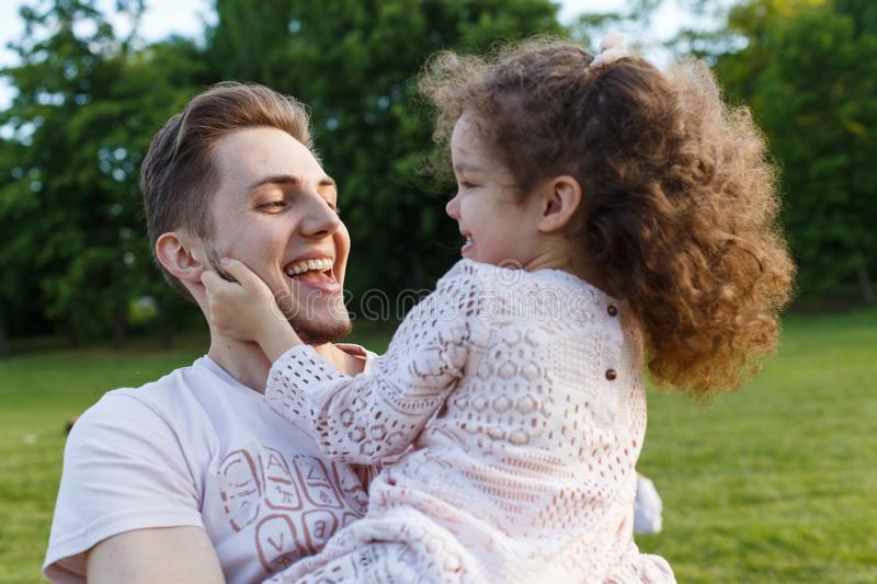 Family, parenthood, fatherhood and people concept - happy man and little girl in having fun in summer park. Cute curly girl. Family, parenthood, fatherhood and royalty free stock image