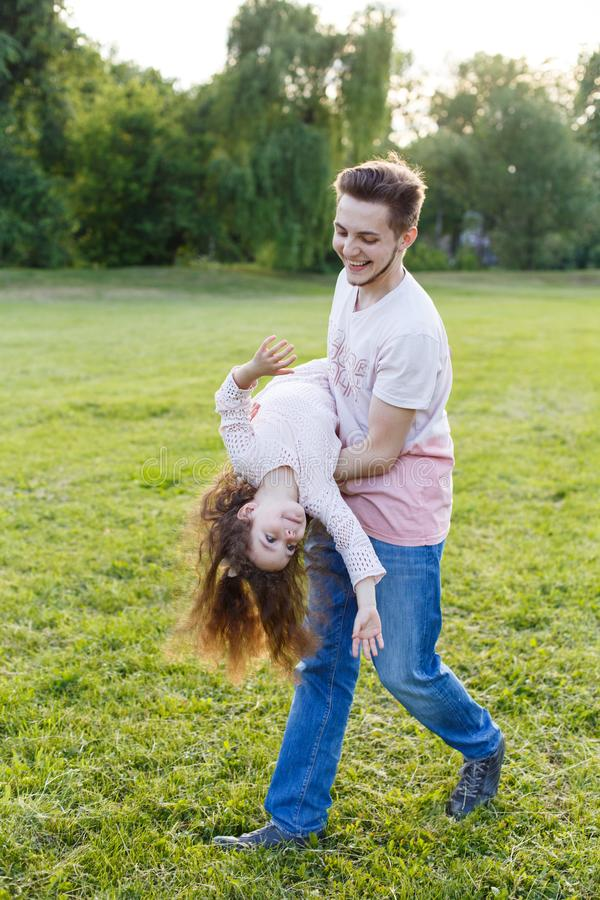 Family, parenthood, fatherhood and people concept - happy man and little girl in having fun in summer park. Cute curly girl. Family, parenthood, fatherhood and royalty free stock photography