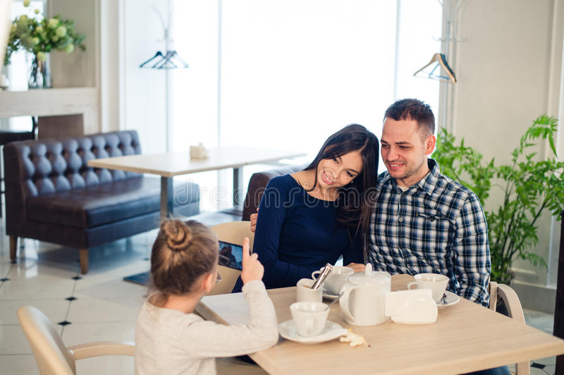 Family, parenthood, technology people concept - close up of happy mother, father and little girl having dinner, kid stock photo