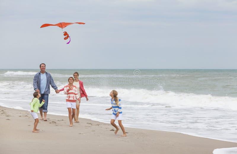 Family Parents Girl Children Flying Kite on Beach stock photos