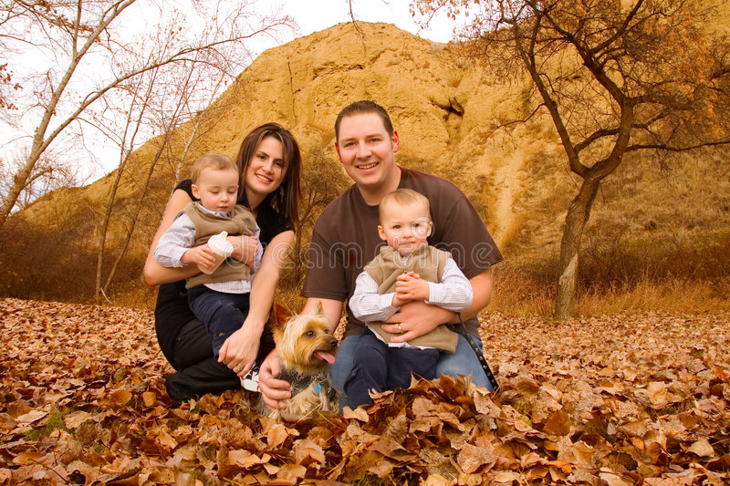 Family at the park. Family with twin boys and pet dog at a park in Autumn