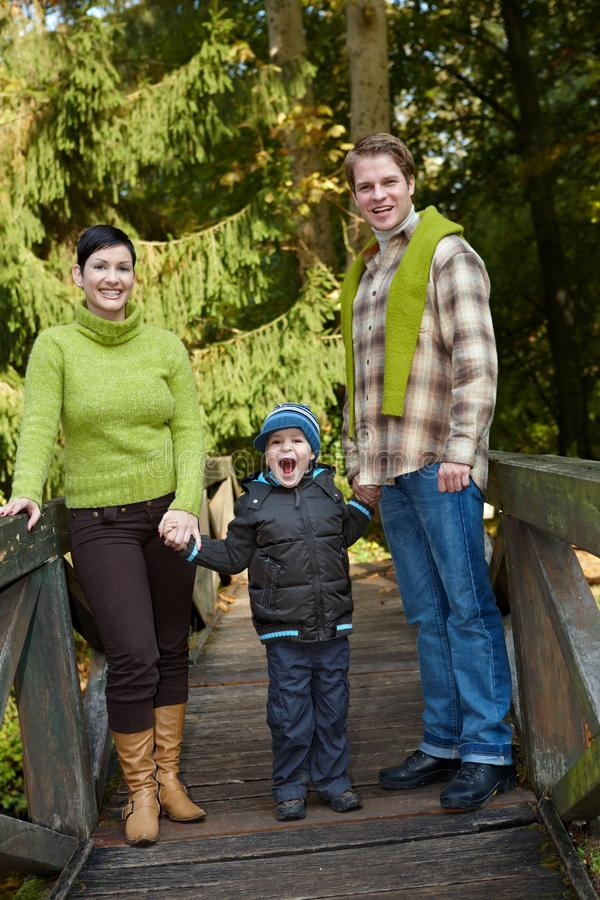 Family in park. Young happy family of three standing in park on bridge, holding hands, laughing stock photography