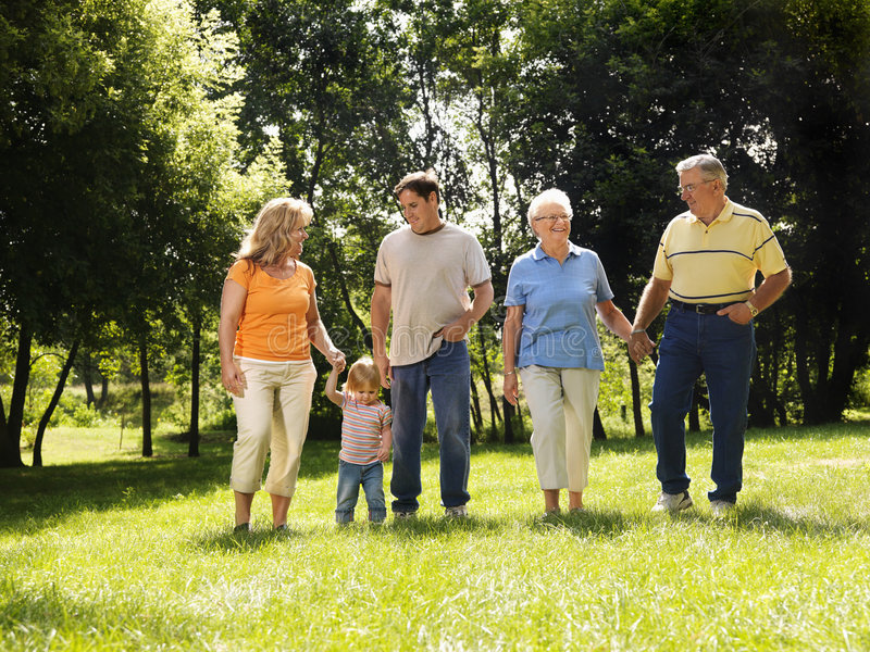 Family in park. Three generation Caucasian family holding hands walking across grass in park smiling stock photos