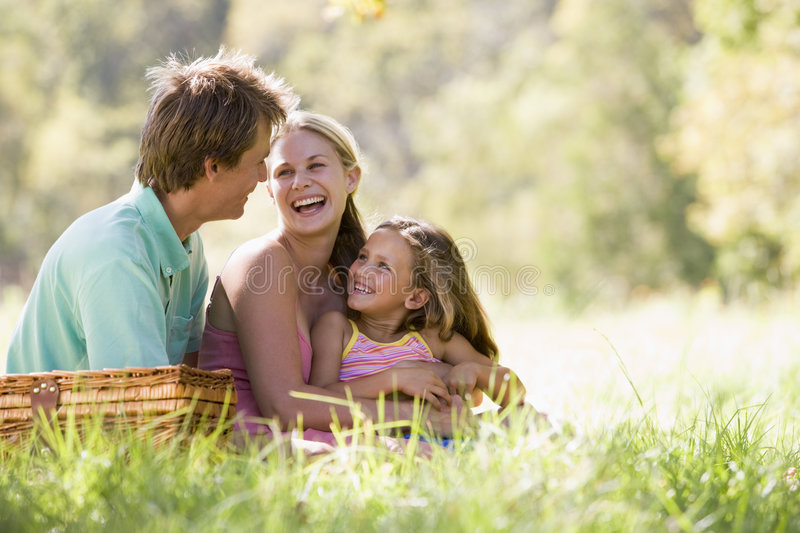 Family at park having a picnic and laughing. With each other royalty free stock photography