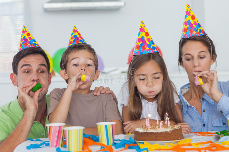Family with party horn celebrating their daughter party stock photography