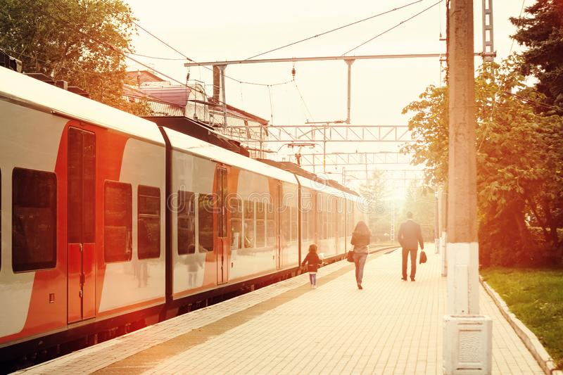 Family of passengers of a train arriving on the platform disappears into the distance in the light of sunset royalty free stock image