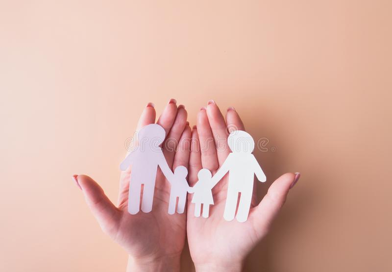 Family on a peach background made of white paper. Mom Dad Daughter and Son. There is a place for inscription. The idea of ?? stock photos