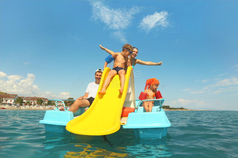 Family on pedal boat with yellow slide in sea stock photos
