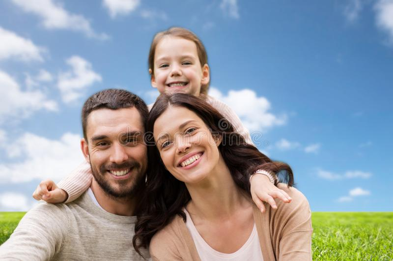 Happy family over blue sky and grass background royalty free stock image