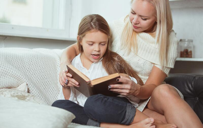 Mom and daughter read a book at home. stock photo