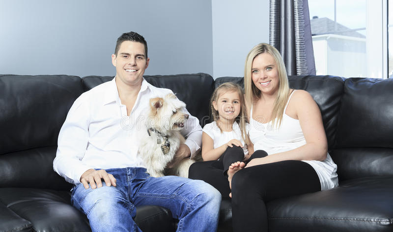 Family with pets sit on sofa at home royalty free stock photo