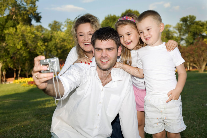 Family photo. Father taking a photo of whole family at the park on a sunny day