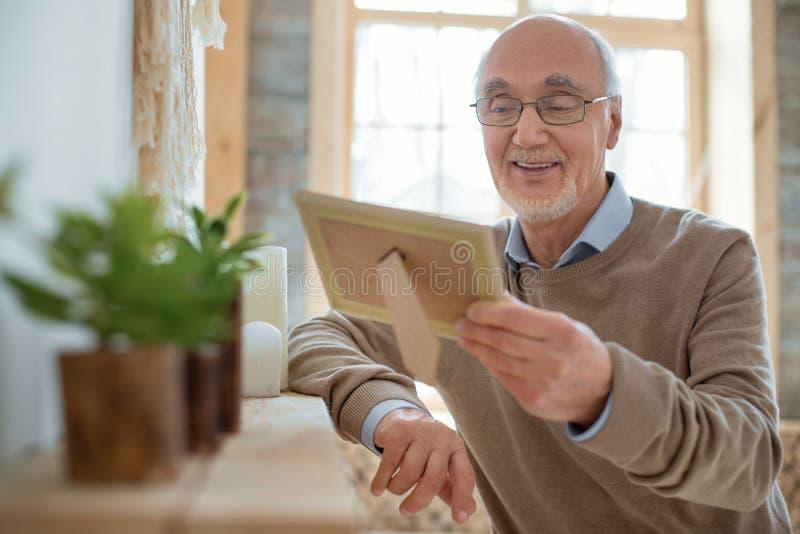 Glad senior man admiring photo stock images