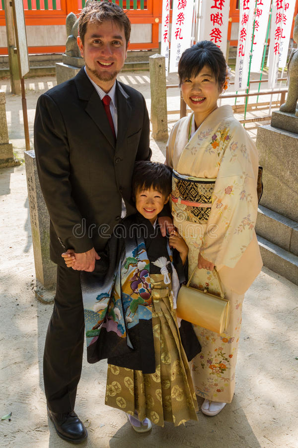 7-5-3 Family Photo. An international couple, White and Japanese, pose with their child in suit and kimono in front of a shrine for a 7-5-3 Ceremony, a rite of royalty free stock images