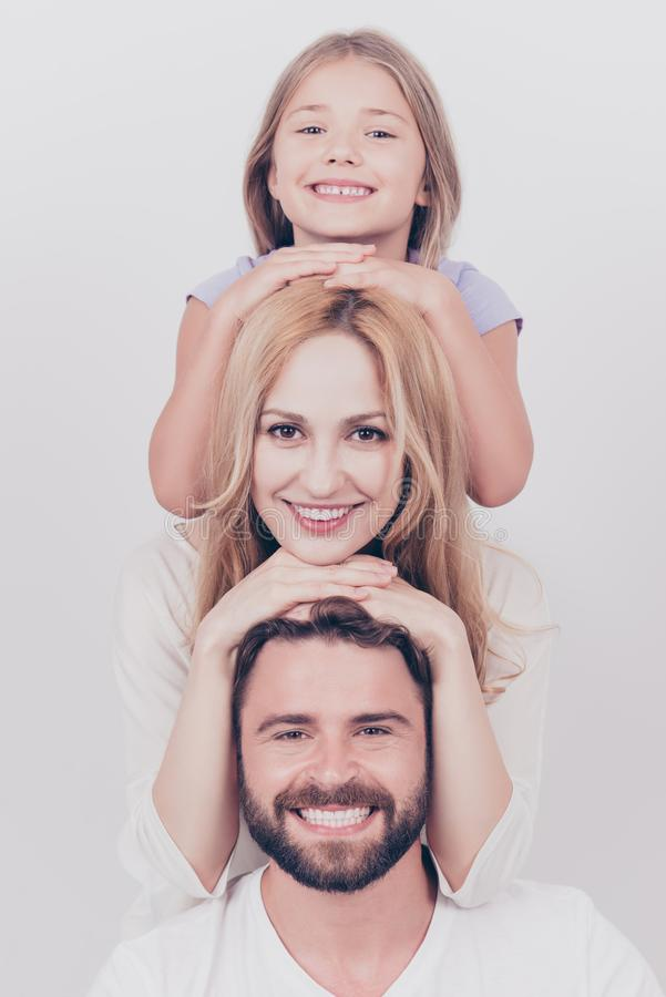 Family photo portrait of three. Parents and small blond daughter. Are posing on the white background, smiling, putting each others head on top of each other stock photography