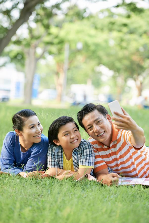Family photographing in park. Cheerful mature Asian man taking photo with his family when they are resting in park stock images