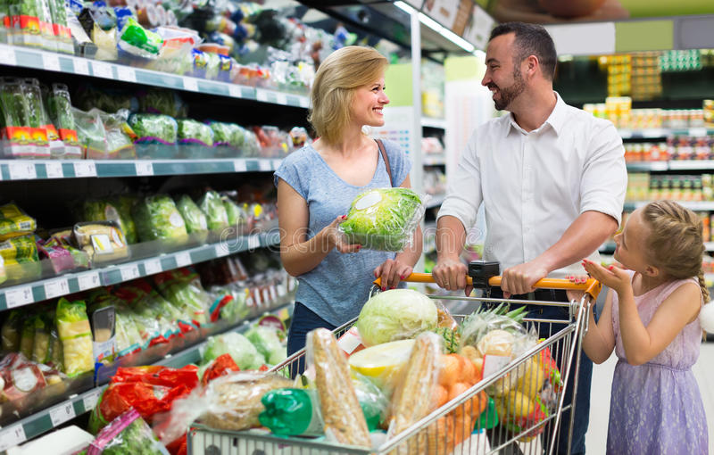 Family picking greens in food store stock photos