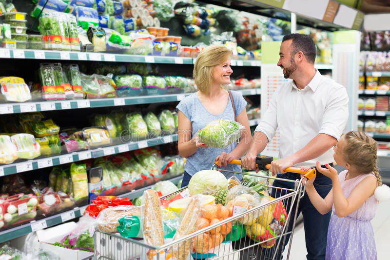 Family picking greens in food store stock image