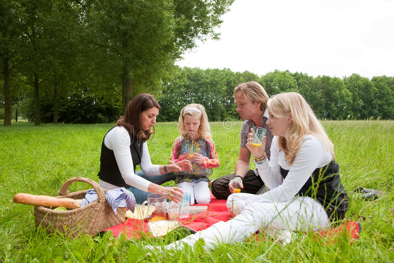 Family picnic. Pretty young family on an outdoors picnic in the field stock photo