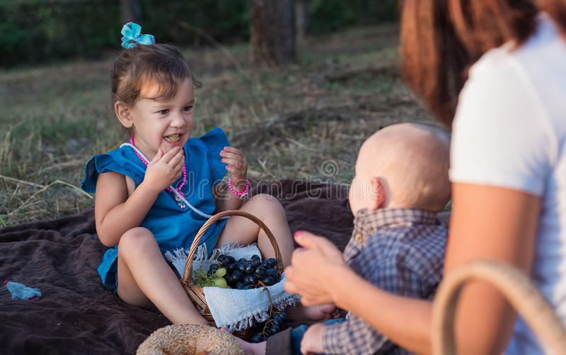 Family picnic in autumn in the apple garden. A little funny girl stock images