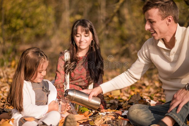 Family picnic in the autumn park. Family drinking tea royalty free stock image