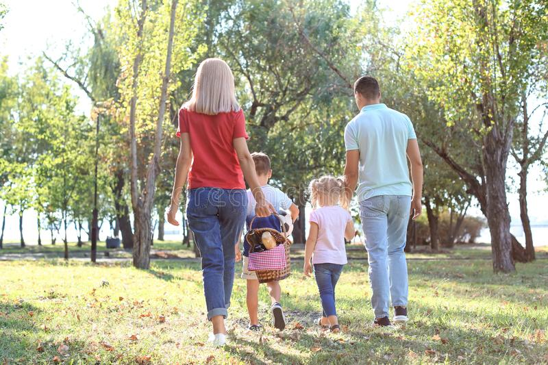 Family with picnic basket in park stock photo