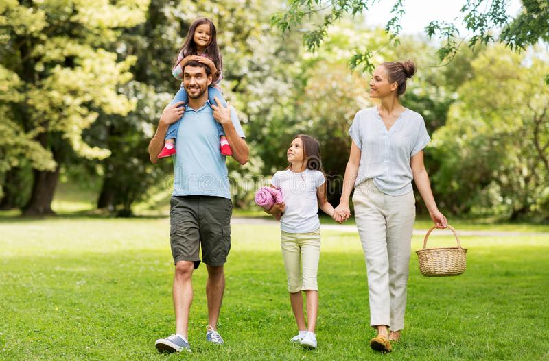 Family with picnic basket walking in summer park stock images