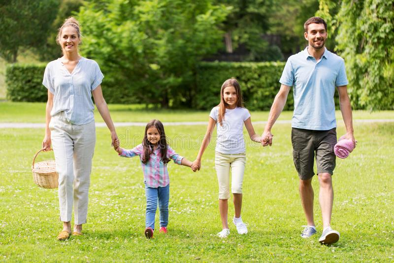 Family with picnic basket walking in summer park stock photos