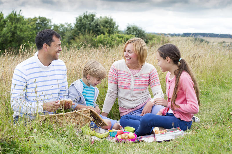 Family picnic at the beach. A family of four are sat on the sand dunes having a picnic stock images