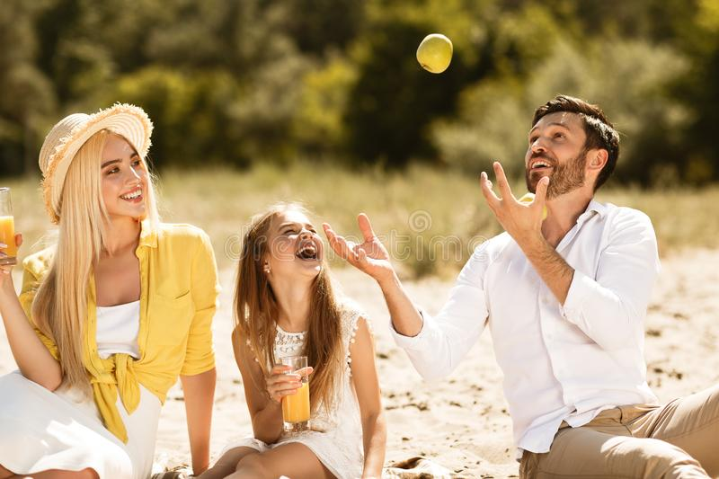 Family on picnic, father juggling with apples. Enjoying weekends in nature royalty free stock images
