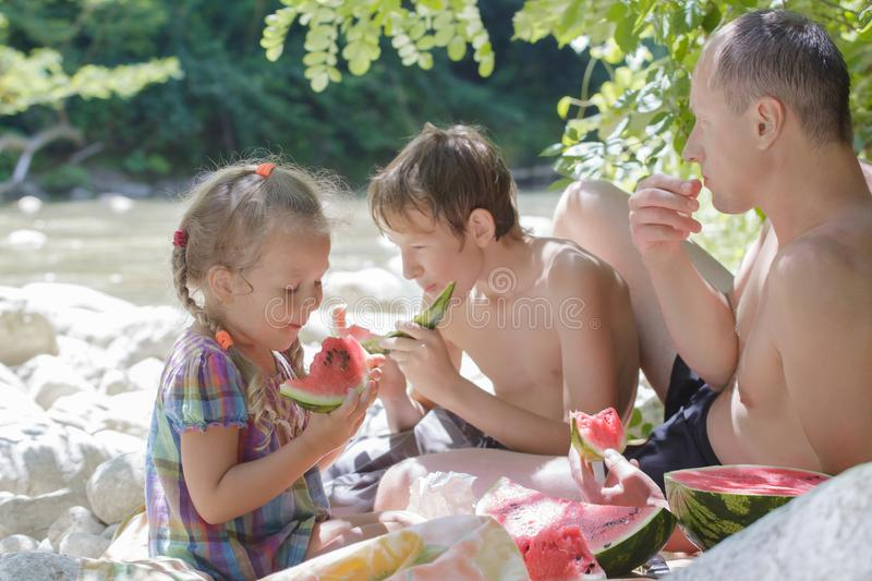 Family picnic of father and two children with juicy watermelon. In hot summer day stock photo