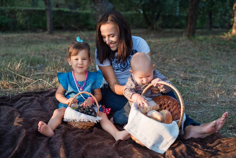 Family picnic in the garden tonight. Beautiful young mother and children royalty free stock photos