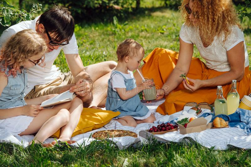 Family picnic on grass in the gardens under gentle shade of trees stock photos