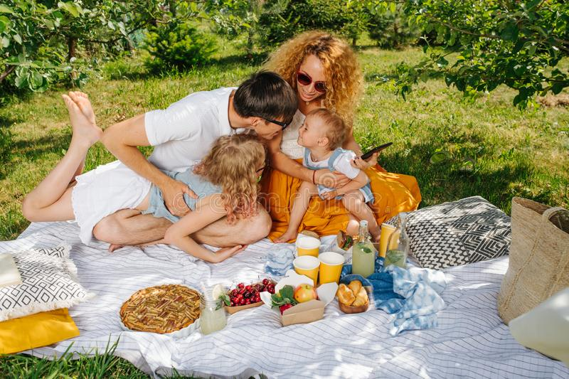 Family picnic on grass in the gardens under gentle shade of trees stock photo