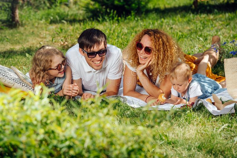 Family picnic on grass in the gardens under gentle shade of trees royalty free stock image