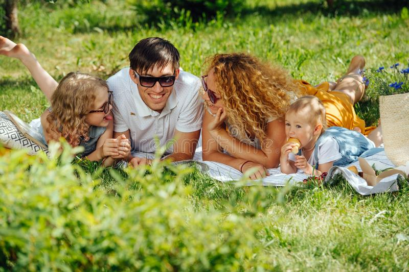 Family picnic on grass in the gardens under gentle shade of trees stock photography