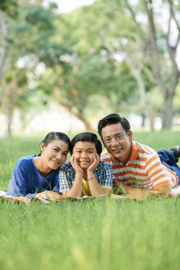 Family picnic. Happy parents and their teenage son lying on grass in park and smiling at camera royalty free stock photography