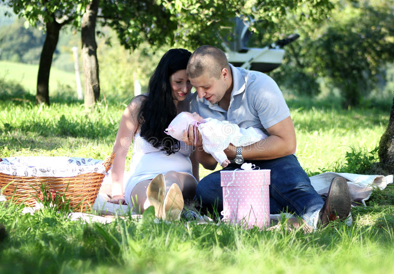 Family picnic. Happy family with their newborn baby sitting in park on grass having a picnic smiling stock image