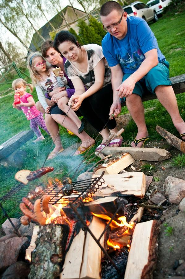 Family picnic. A family having a picnic and grilling sausages on open fire royalty free stock photography