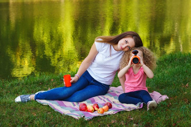 Family picnic. Mother and daughter are sitting on bedspread on bank of river. Little girl is drinking from thermos. Apples lie on royalty free stock photos