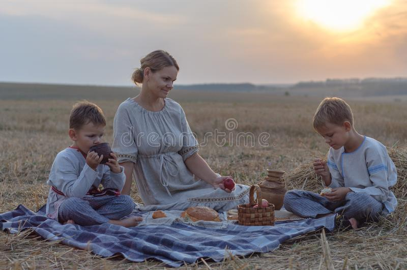 Family picnic in nature. mother and children eat on a sloping wheat field royalty free stock photo