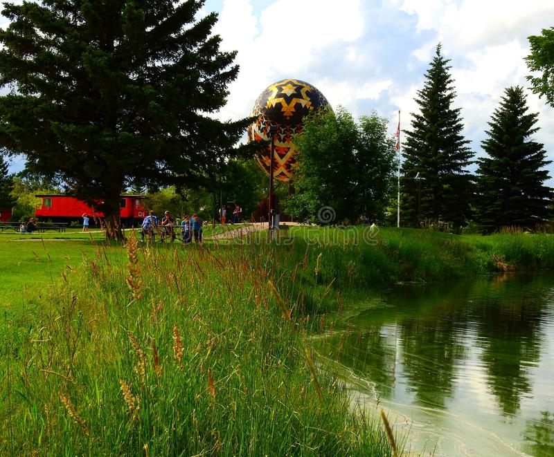 Family picnic in a park with a giant sculpture of a pysanka royalty free stock photography
