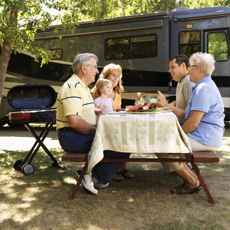 Family at picnic table. Three generation Caucasian family seated at picnic table in front of recreational vehicle talking royalty free stock photography