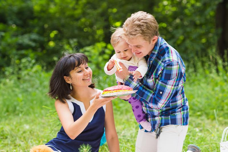 Family picnicking outdoors with their cute daughter stock image