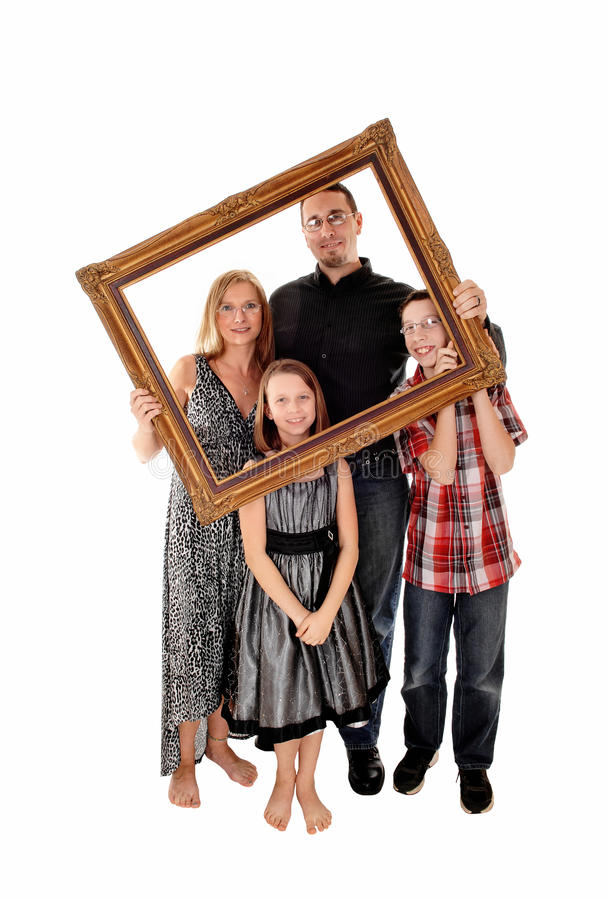 Family in picture frame. A young lovely family standing for white background and holding a picture frame in front of them stock photos