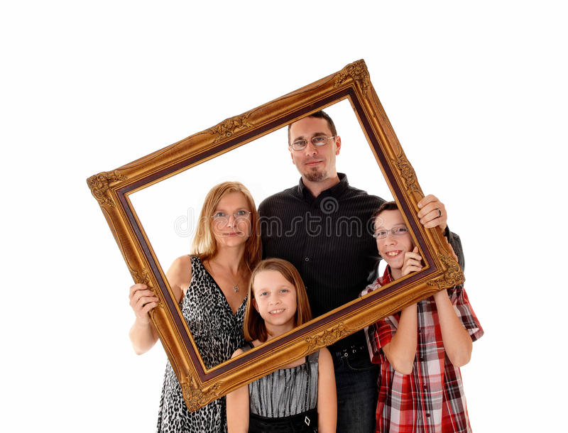 Family in picture frame. A young lovely family standing for white background and holding a picture frame in front of them stock photo