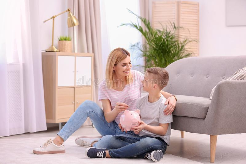 Family with piggy bank and money at home stock photos