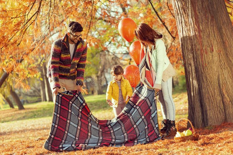 Family placing a picnic blanket royalty free stock image