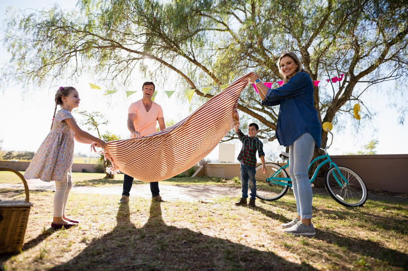 Family placing picnic blanket on in the park royalty free stock images