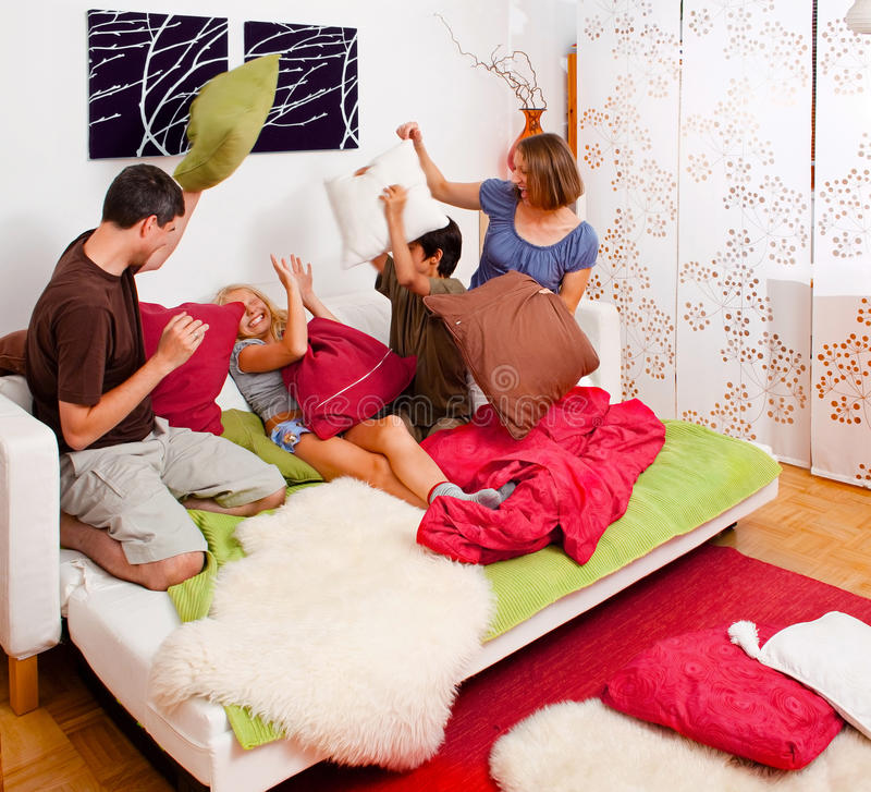 Family-playground 04. A young family is making a pillow-fight in their bedroom stock photography